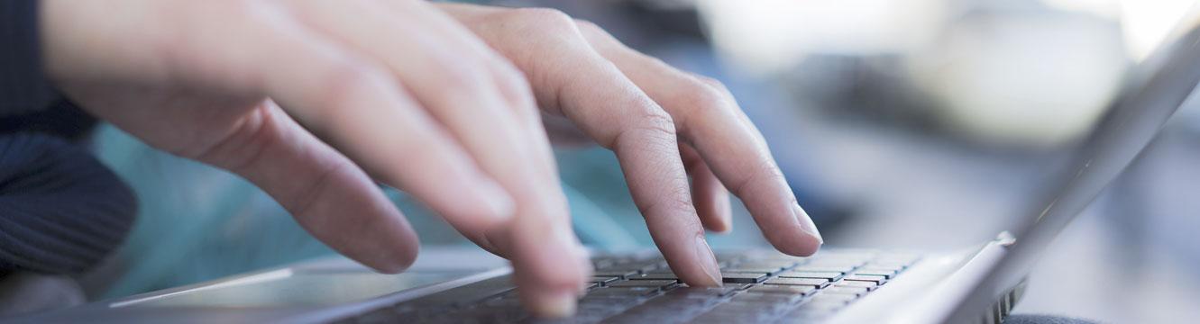 Une personne rédige une email sur son ordinateur