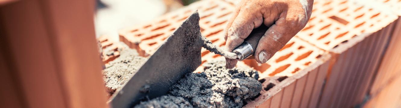 Un maçon travaille sur les fondations d'un bâtiment