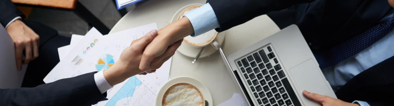 Deux hommes se serrent la main après un entretien réussi, le tout devant un ordinateur et des cafés
