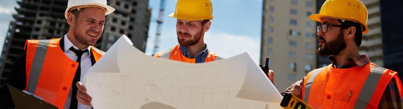 Trois personnes regardent un plan sur un chantier