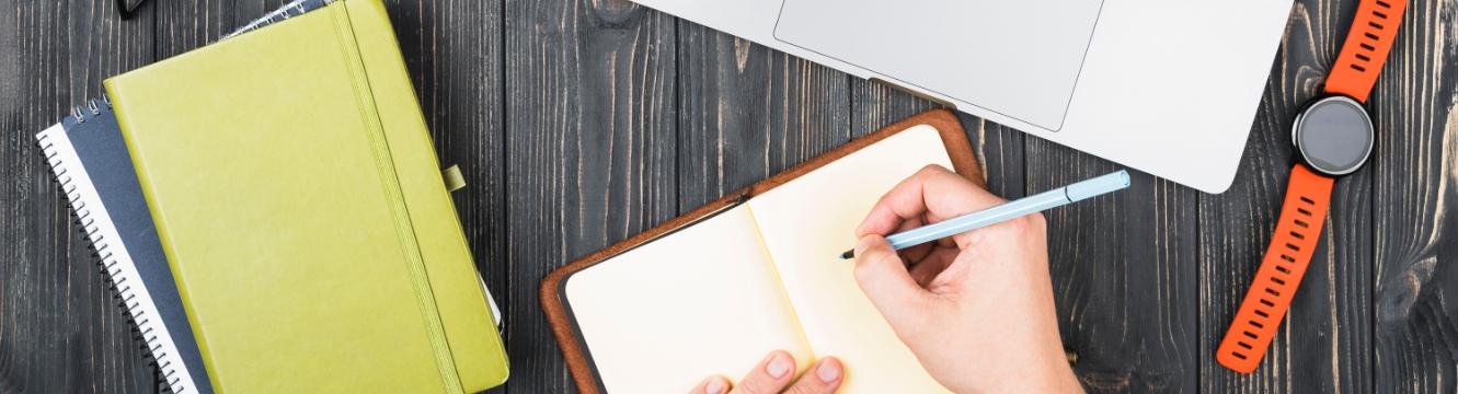 une personne écrit sur un carnet devant un ordinateur portable
