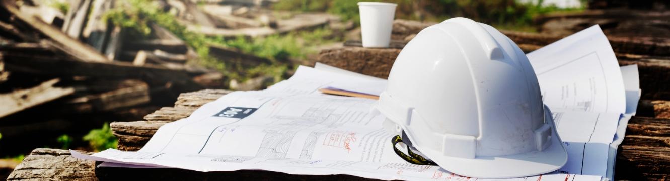 Un casque de chantier est posé sur un plan d'architecture