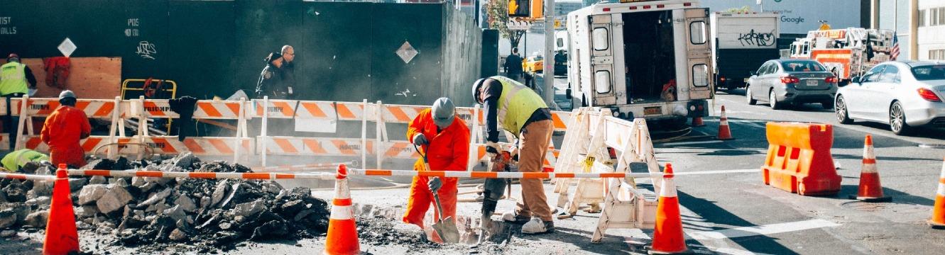 Deux employés de chantier travaillent dans une rue